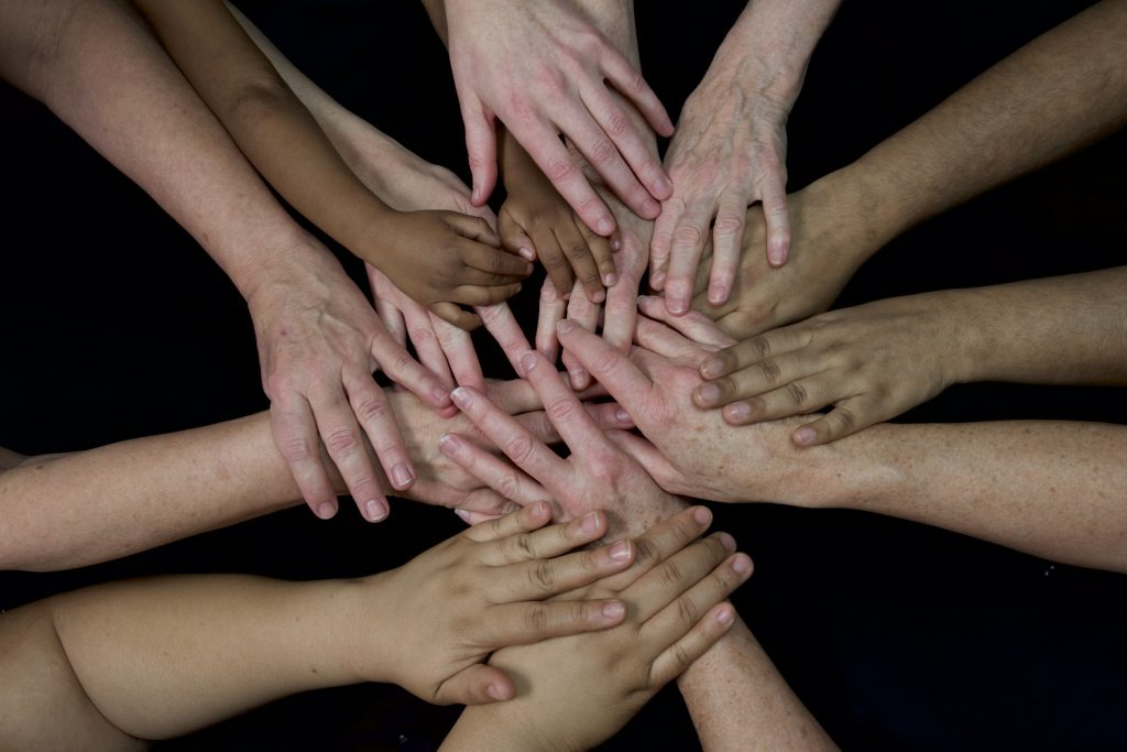 Large group of ethnically diverse human hands in a circle
