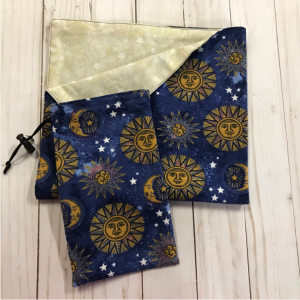 drawstring bag and reading cloth made from dark blue fabric with golden suns lined with a light gold fabric